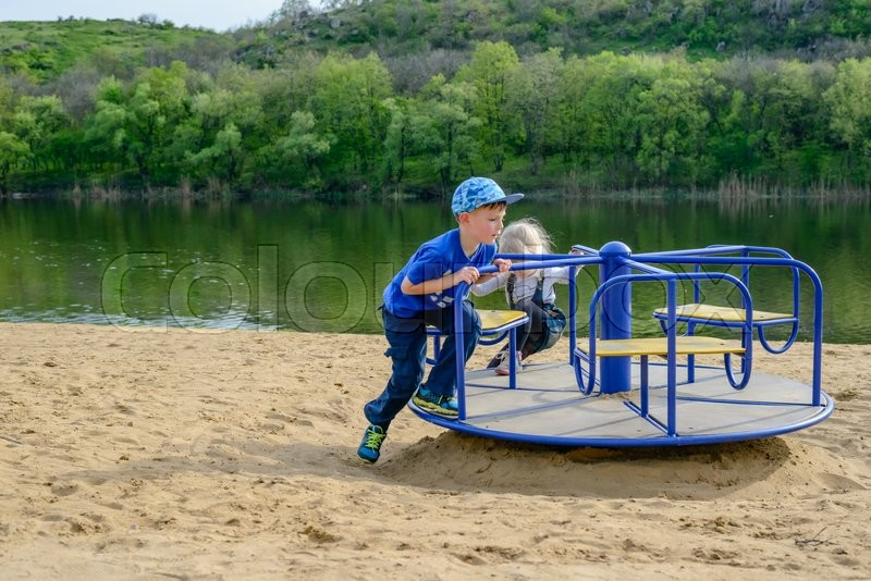 Stock image of 'Two laughing children playing on a small blue merry-go-round on a sandy beach alongside a river as they enjoy their summer vacation'
