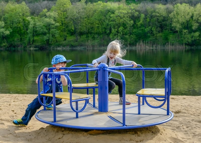Stock image of 'Two young children playing on a merry-go-round on the banks of a river or lake pushing themselves around to gain speed'