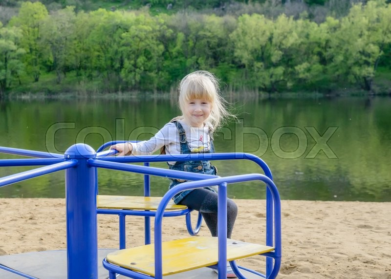 Stock image of 'young kid playing on a blue merry-go-round on a sandy beach alongside a lake as they enjoy their summer vacation'