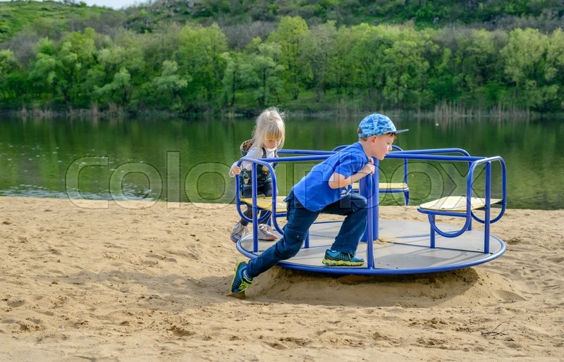 Stock image of 'Little boy pushing a small blond girl on a merry-go-round on a sandy beach alongside a lake or river laughing with glee'