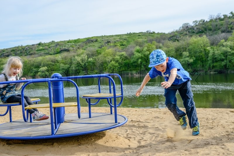 Stock image of 'Boy running alongside a merry-go-round as he spins a little girl around at speed on an outdoor sandy playground alongside a lake'
