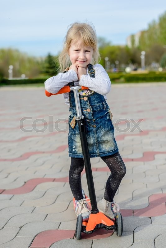 Stock image of 'Smiling little blond girl posing on a toy scooter resting her arms and chin on the handlebars, front view on a paved outdoor square'