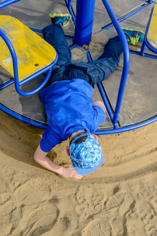 Stock image of 'Young boy drawing a circle in the sand as he leans over the side of a spinning merry-go-round , high angle view'