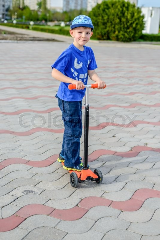 Stock image of 'Handsome stylish young boy dressed in blue standing on a toy scooter on a paved urban park smiling at the camera'