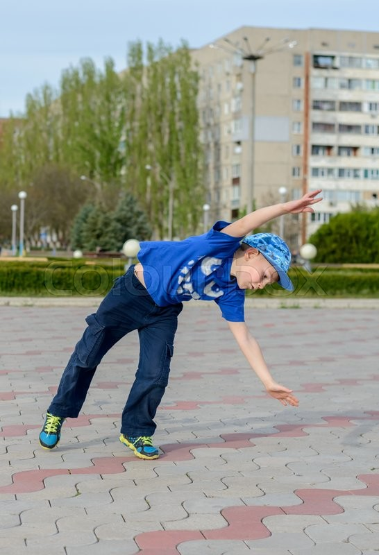 Stock image of 'Little boy preparing to do a cartwheel tipping himself to the side on a paved area in an urban park'