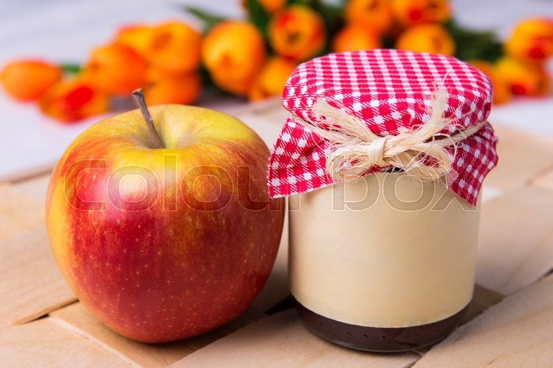 Stock image of 'close up of jar of jam or honey and red apple'