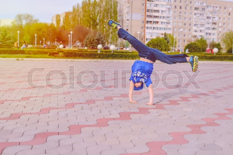 Stock image of 'Small boy in a trendy blue outfit doing cartwheels on a paved urban square balancing on his hands'