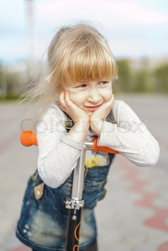 Stock image of 'Tired thoughtful pretty young blond girl on a toy scooter resting her arms on the handlebars with her chin in her hands'