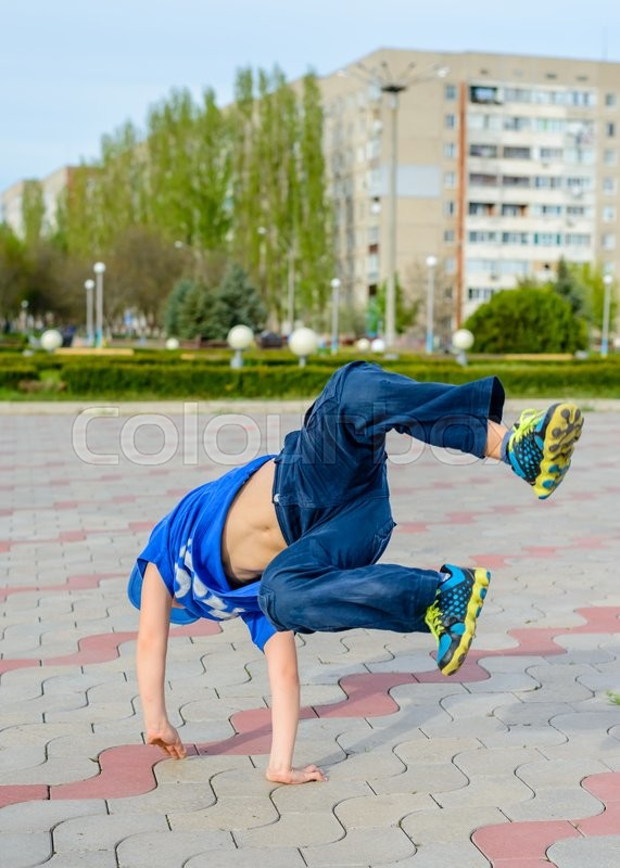 Stock image of 'Agile young boy in a trendy blue outfit doing cartwheels in a paved urban square balancing on his hands'