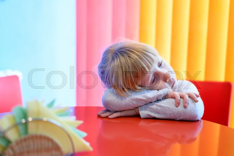Stock image of 'Tired little girl with her head resting on her arms on the table against a colorful pink and yellow backdrop'