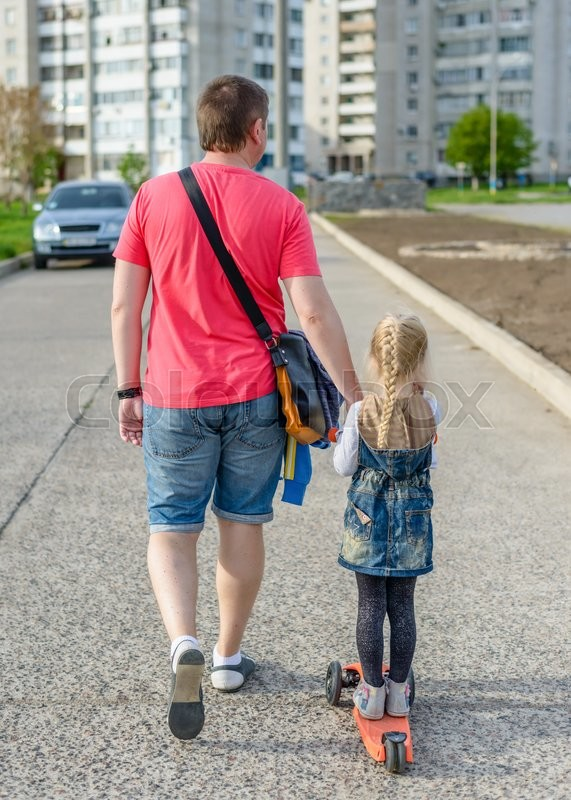 Stock image of 'Father pulling his small daughter along on a scooter as they walk along an urban road towards apartment blocks, rear view'