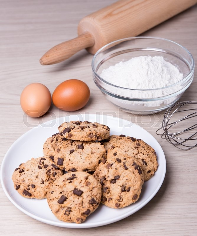 Stock image of 'bakery concept - ingredients for cooking chocolate chip cookies on wooden table background'
