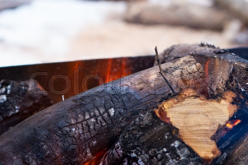 Stock image of 'Flames and smoke from burning wood Burning firewood with ashes and flames close-up'