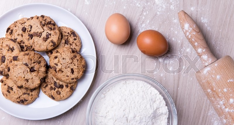 Stock image of 'close up of ingredients for cooking chocolate chip cookies on wooden table'