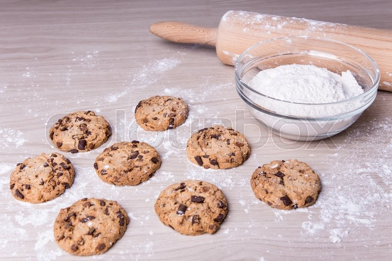 Stock image of 'fresh baked chocolate chip cookies on wooden table with flour'