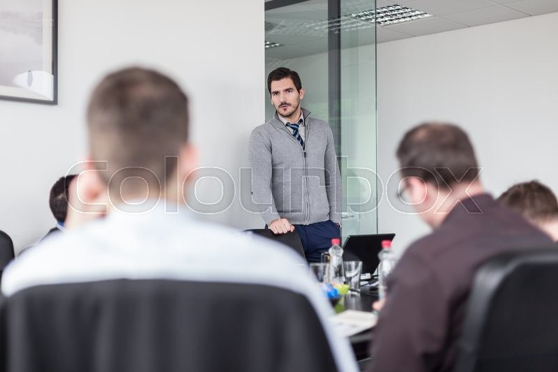 Stock image of 'Team manager and business owner leading in-house business meeting. Business and entrepreneurship concept.'