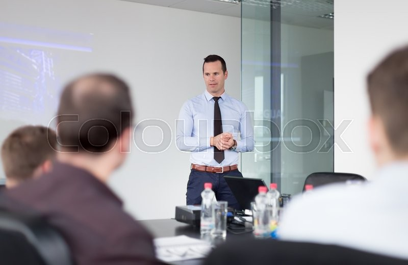 Stock image of 'Business man making a presentation at office. Business executive delivering a presentation to his colleagues during meeting or in-house business training, explaining business plans to his employees.'