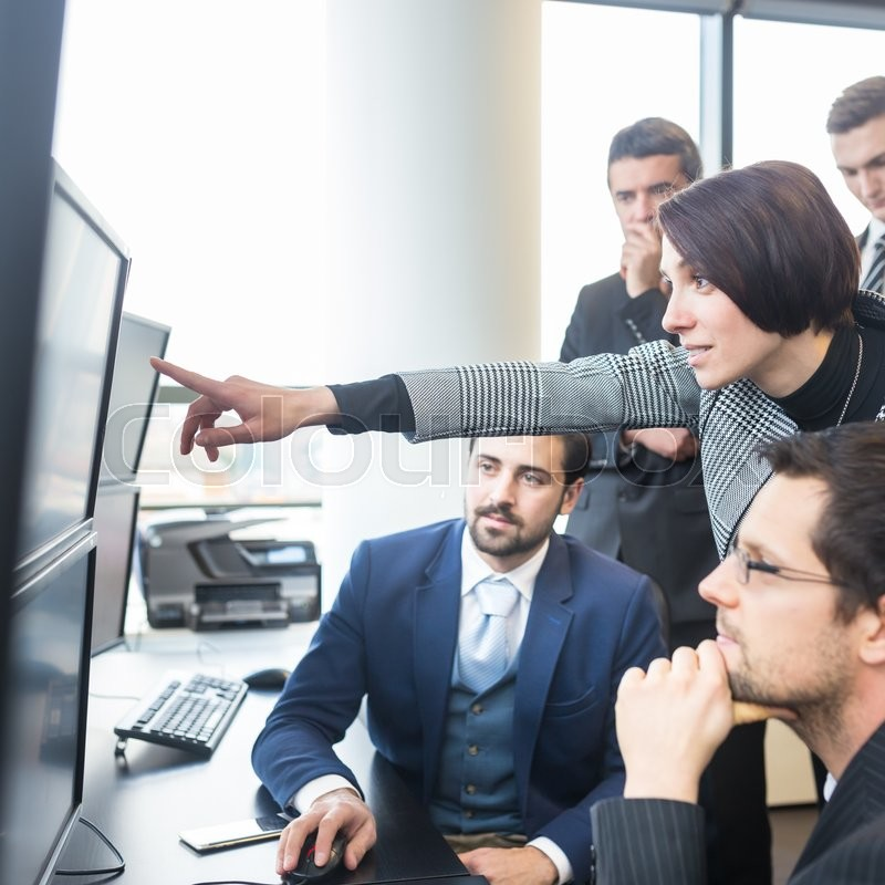 Stock image of 'Business team looking at data on multiple computer screens in corporate office. Businesswoman pointing on screen. Business people trading online. Business, entrepreneurship and team work concept.'