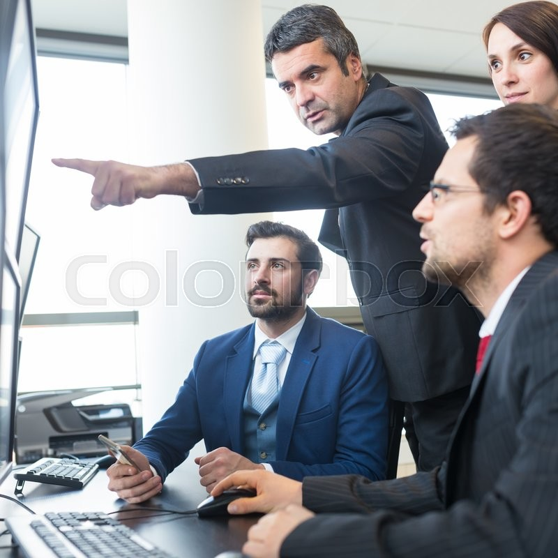 Stock image of 'Business team looking at data on multiple computer screens in corporate office. Businessman pointing on screen. Business people trading online. Business, entrepreneurship and team work concept.'