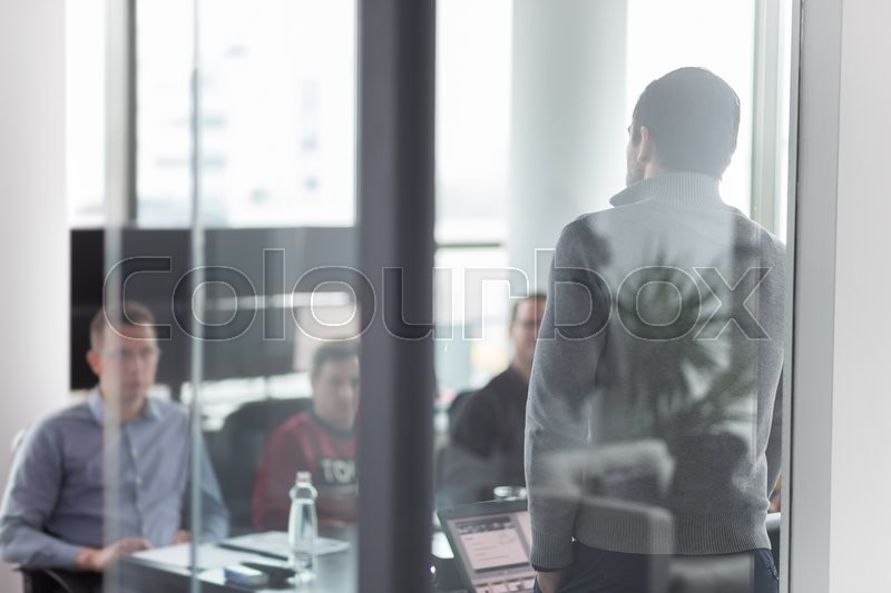 Stock image of 'Businessman making a presentation at office. Business team leader delivering a presentation to his colleagues during meeting or in-house business training.'