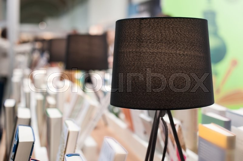 Stock image of 'Electric brown table reading lamp and books in a library.'