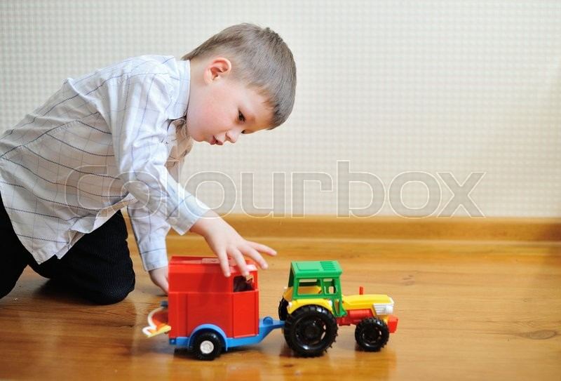 Stock image of 'child boy toddler playing with toy car indoors.'