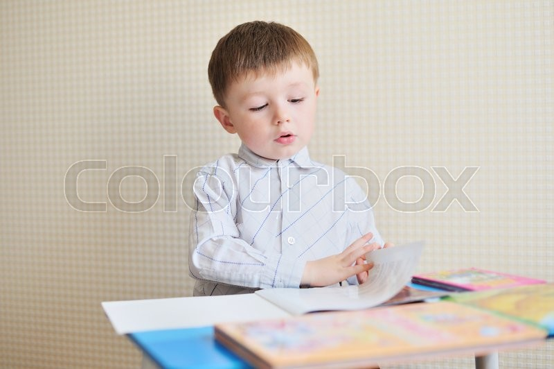 Stock image of 'Portrait of cute boy with pen and paper at desk in classroom.'