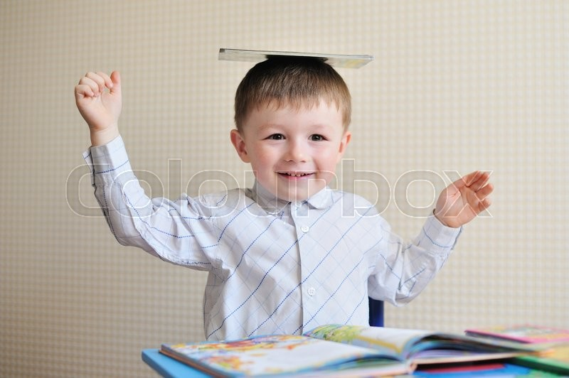 Stock image of 'Young schoolboy playing with books and smiling as he sits at his desk in classroom.'