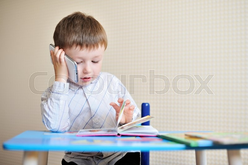 Stock image of 'little boy is sitting at a desk in school and speaking on the phone.'