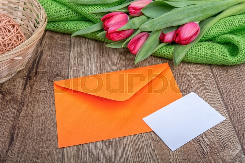 Stock image of 'Envelope with sheet of paper and red tulips on a wooden background'
