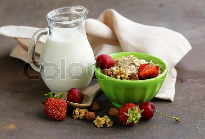 Stock image of 'Oatmeal, milk, berries and nuts for healthy food'