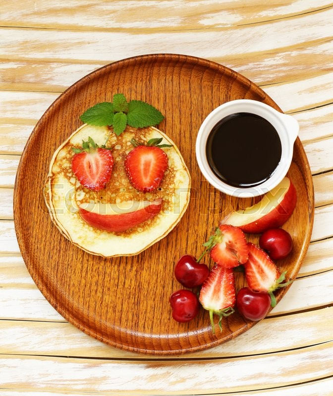 Stock image of 'Breakfast pancakes with berries (strawberry, cherry, banana), funny face'