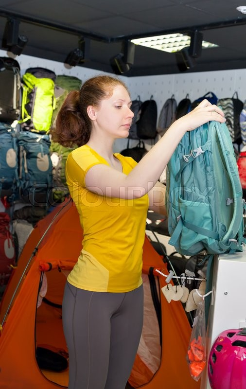 Stock image of 'Young girl in yellow t-shirt picks Tourist backpack in the store. Specialized products for tourism and mountaineering. The buyer on the background of shop window with tents and backpacks.'