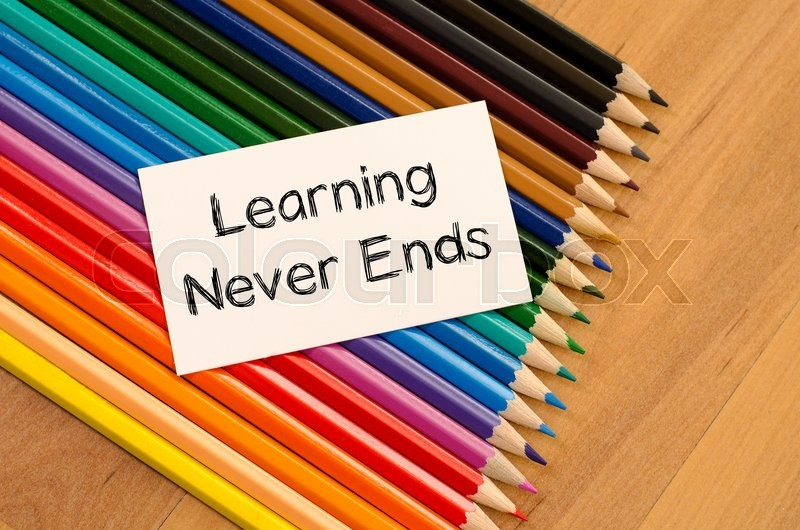 Stock image of 'Learning never ends text concept and colored pencil on wooden background'