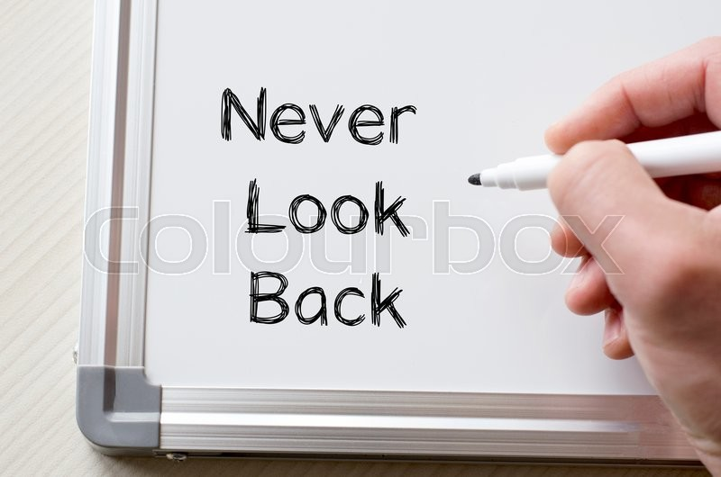 Stock image of 'Human hand writing never look back on whiteboard'