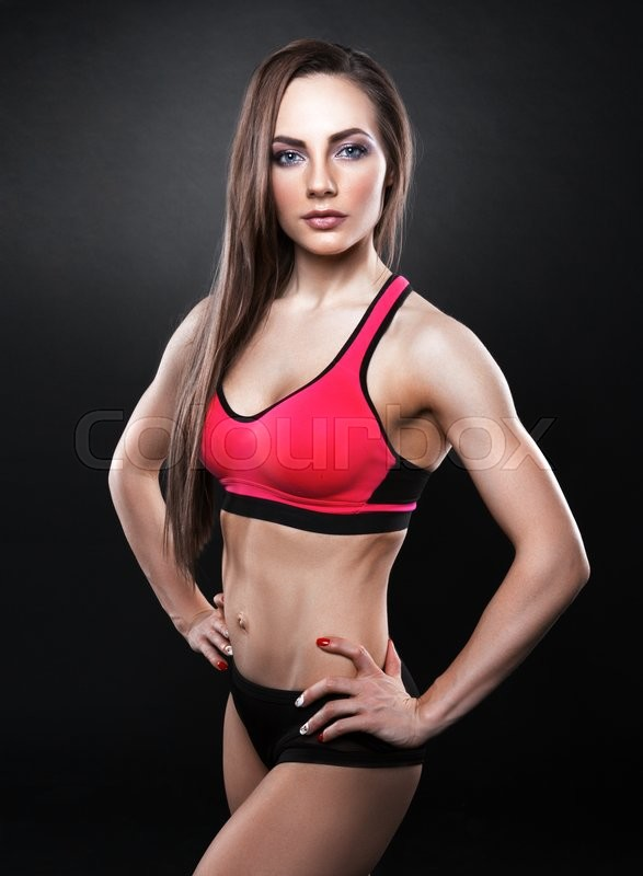 Stock image of 'Sexy young woman standing on grey background. Fitness female looking at camera. Concept of sport and healthy lifestyle.'