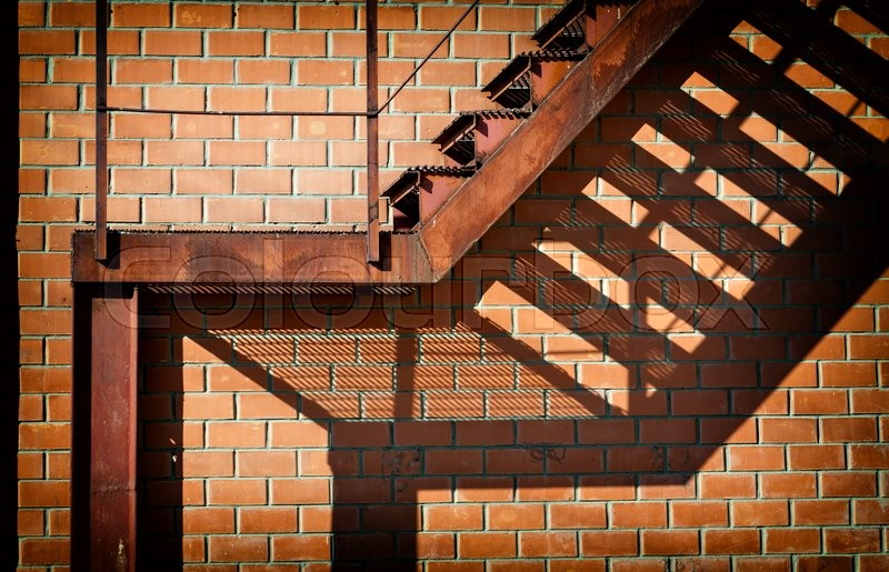 Stock image of 'Old and rusty ladder view, technical output of the building. Brick wall and staircase leaves shadow..'