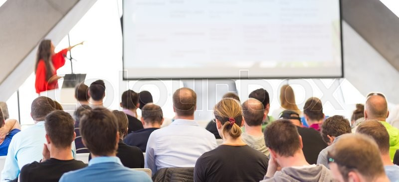 Stock image of 'Woman giving presentation in lecture hall. Male speeker having talk at public event. Participants listening to lecture. Rear view, focus on people in audience.'