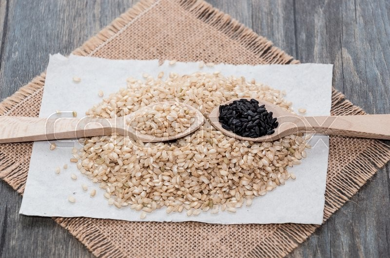 Stock image of 'Brown rice on a tablecloth fabric sack and a wooden spoon'