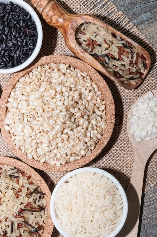 Stock image of 'Several bowls with different rices on a tablecloth'