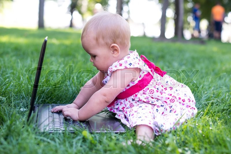 Stock image of 'Baby girl sitting on the green grass with laptop'