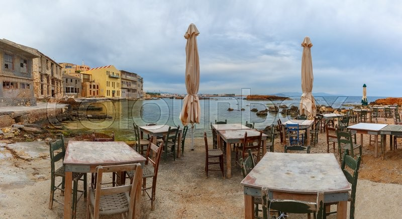Stock image of 'Empty outdoor cafe on the seashore in the cloudy morning, Chania, Crete, Greece'