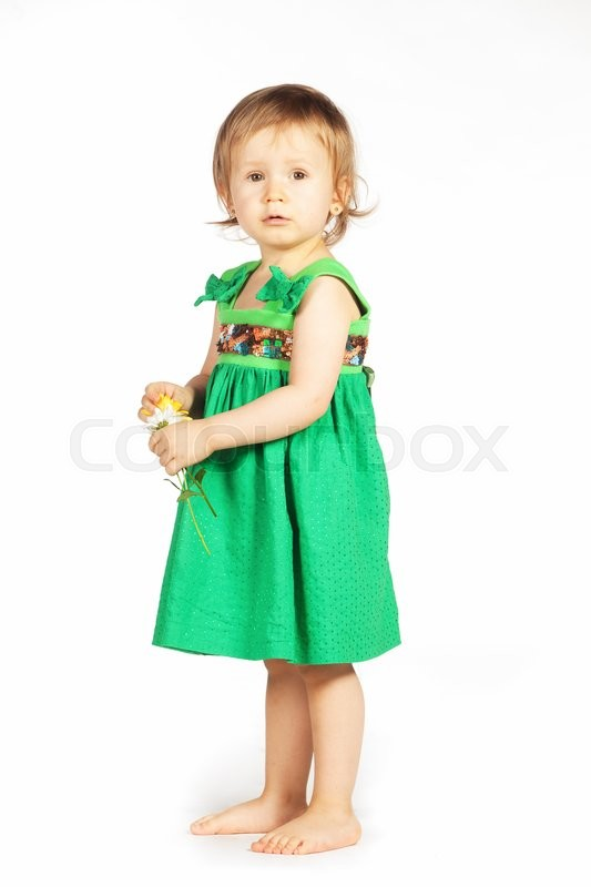 Stock image of 'Little girl in a green dress with yellow flower'