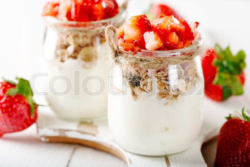 Stock image of 'Strawberries desert with cream and cereals served on glass cups over white table'