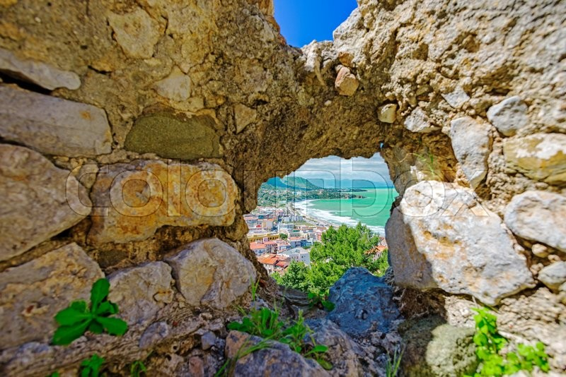 Stock image of 'Aerial view of town Cefalu from above through hole in old stone wall, Sicily, Italy'