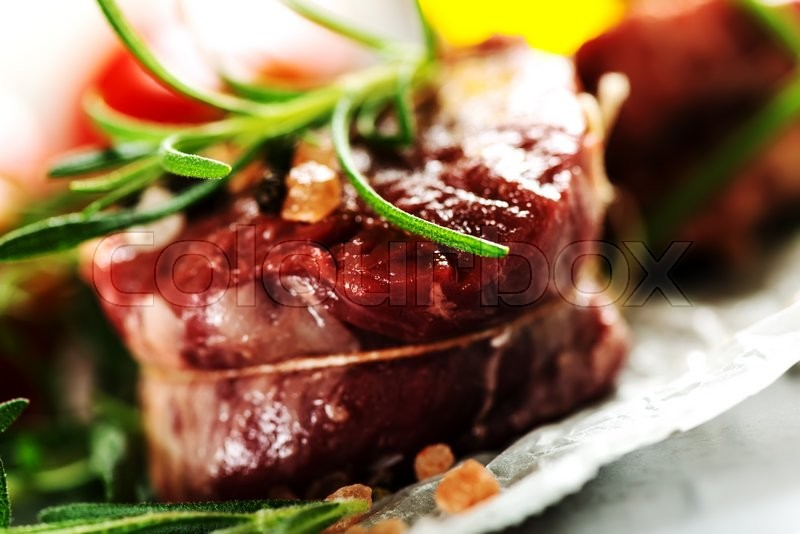 Stock image of 'Raw fresh meat Steak filet mignon and rosemary on cooking paper background'