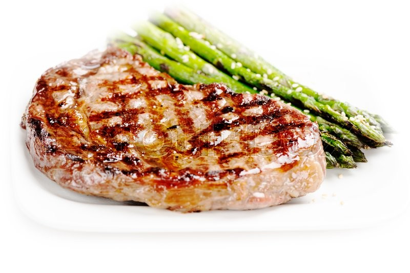 Stock image of 'Barbecue grilled beef steak meat with asparagus on white plate close up'