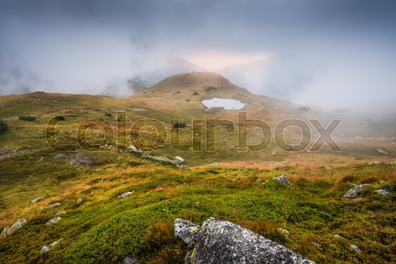 Stock image of 'Mountains Landscape in the Mist with a Tarn and Rocks in Foreground'