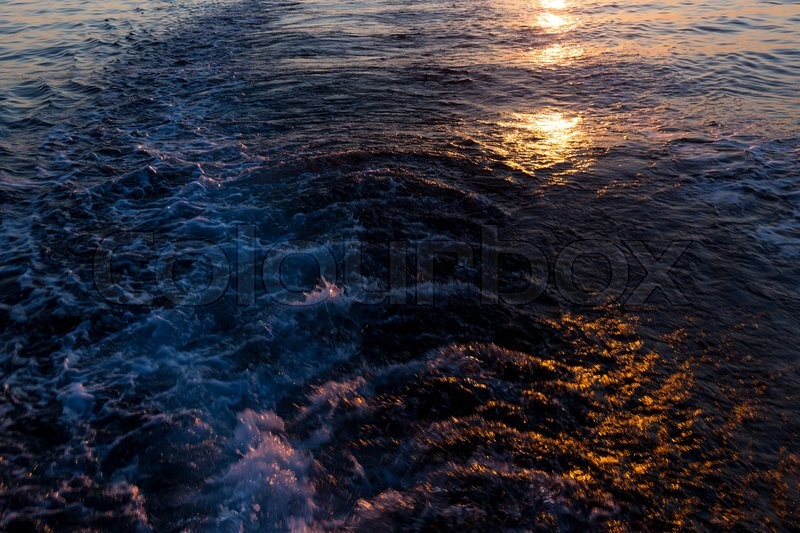 Stock image of 'Sunset in the sea and a trace from the ship'