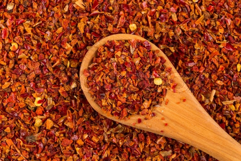 Stock image of 'Crushed red chili pepper and wooden spoon'